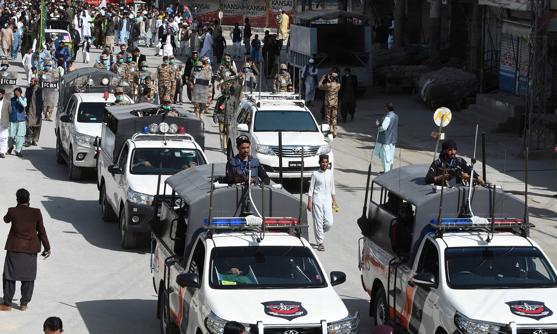 Security personnel escort participants during a rally to celebrate Eid-i-Miladun Nabi in Quetta on October 30. — AFP
