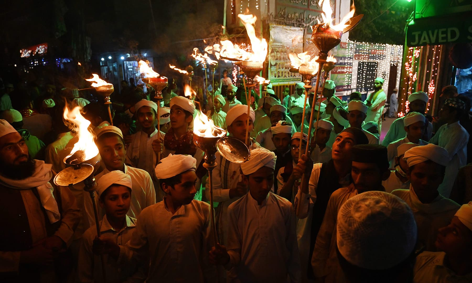 Participants hold torch lights during a rally ahead of celebrations for Eid-i-Miladun Nabi in Lahore on October 29. — AFP