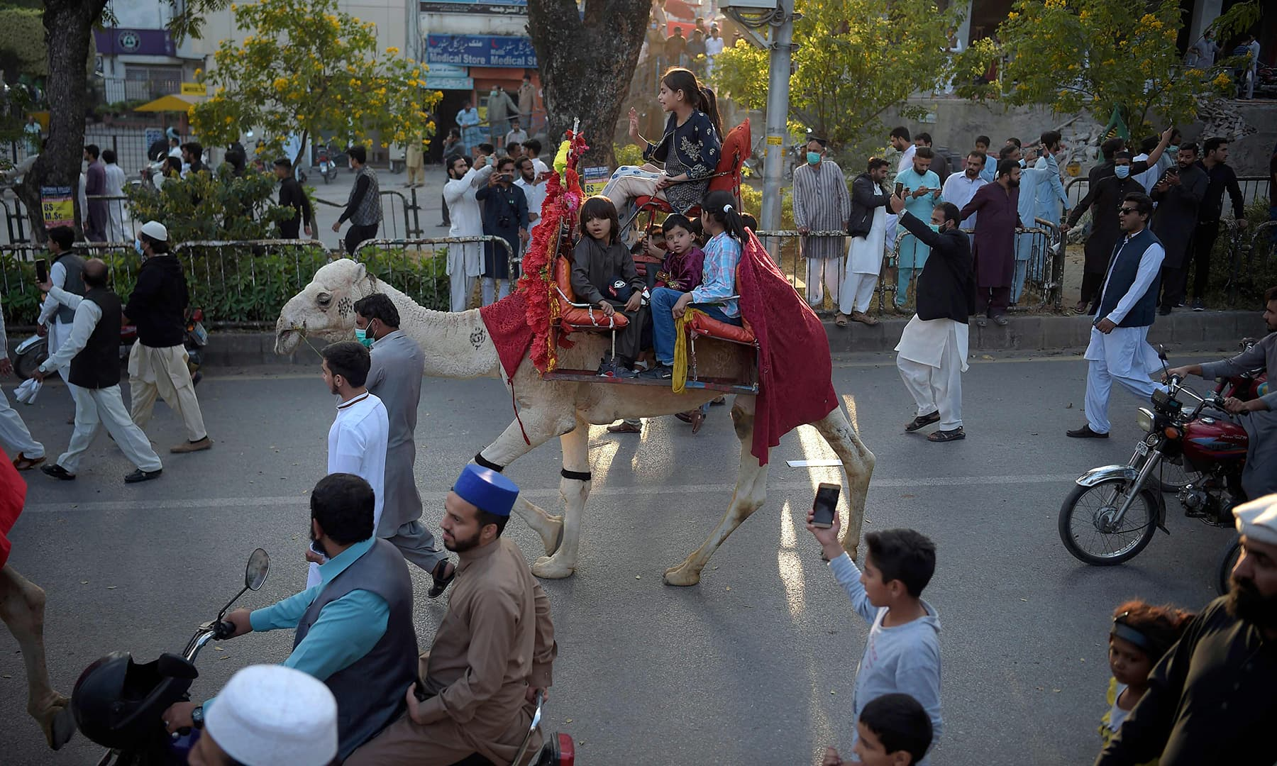 Children ride on a camel during a rally to celebrate Eid-i-Miladun Nabi in Islamabad. — AFP