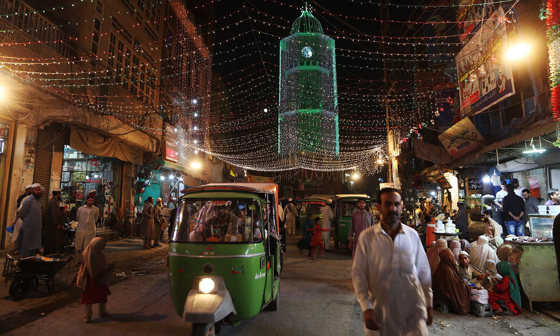 Pedestrians walk along an illuminated street ahead of celebrations for Eid-i-Miladun Nabi in Peshawar on October 29. — AFP