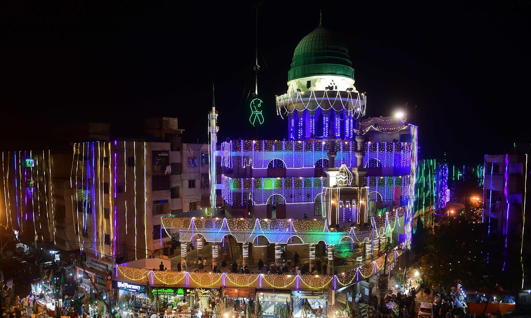 General view of an illuminated mosque and residential apartments ahead of celebrations for Eid-e-Milad-un-Nabi, the birthday of Prophet Mohammad, in Karachi on October 29, 2020. (Photo by Asif HASSAN / AFP) — AFP or licensors