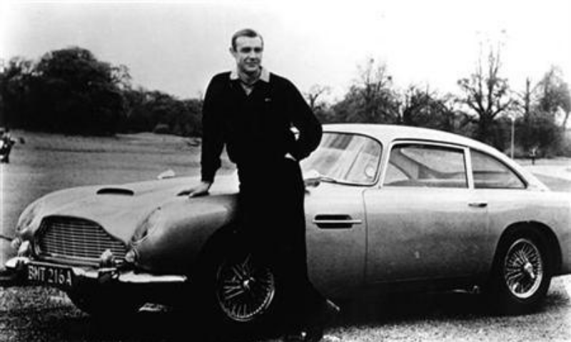 """Sean Connery poses with the Aston Martin from """"Goldfinger"""" in this 1964 photo. — Reuters/File"""