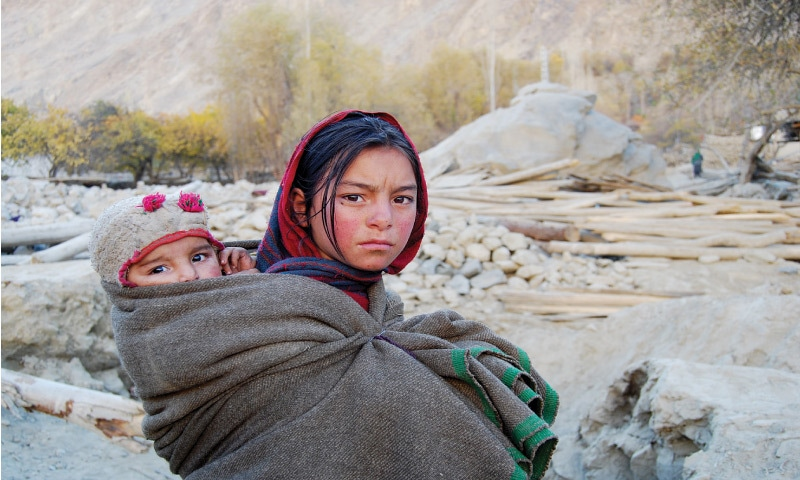 A girl carrying her sibling stands on the rubble of a village destroyed by a land slide in district Ghanche, Baltistan | Photo by the writer