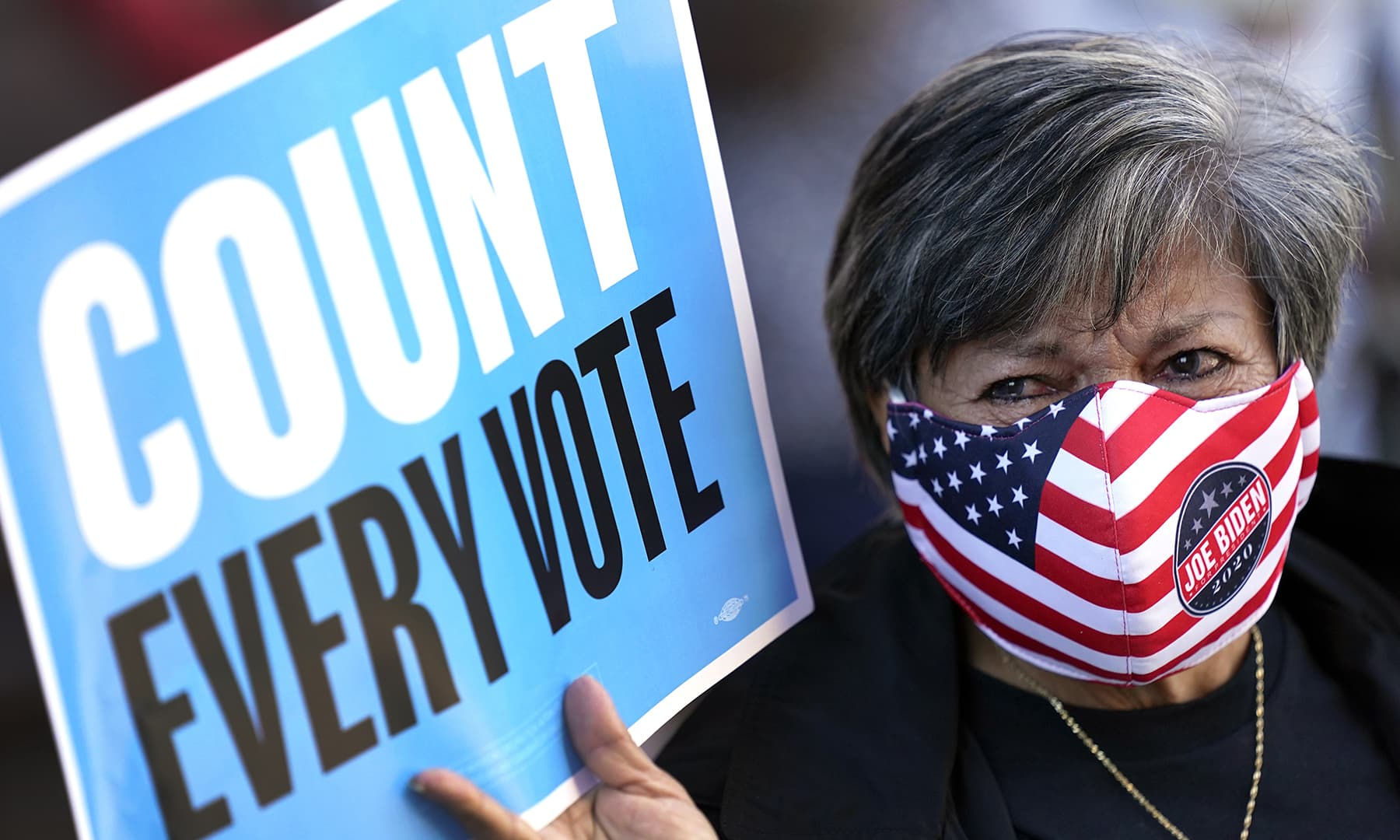 Volunteer election poll worker Cecilia Chaboudy-Dow joins demonstrators as they stand across the street from the federal courthouse in Houston, Monday, Nov 2, before a hearing in federal court involving drive-thru ballots cast in Harris County. — AP