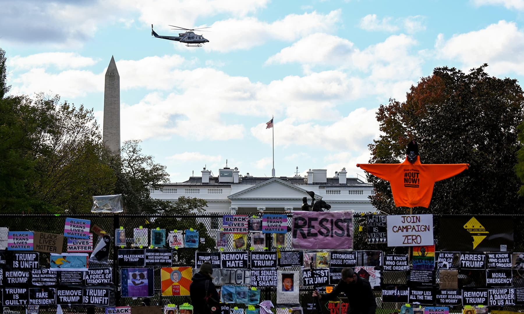 A helicopter passes over the White House, seen behind a fence and protest posters, the day before the US presidential election in Washington, DC, November 2. — Reuters