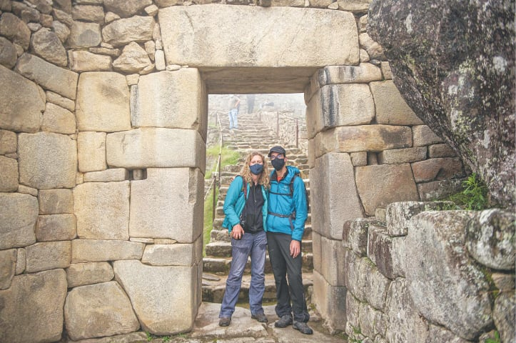 MACHU PICCHU: French citizens Veronique and Arnaud pose for a photo under a door at Machu Picchu, the Inca citadel which has become the crown jewel of Peru's tourist sites.—AFP