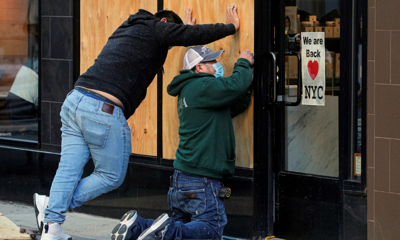 Workers board up a store ahead of election results in the Manhattan borough of New York, US on Nov 2. — Reuters