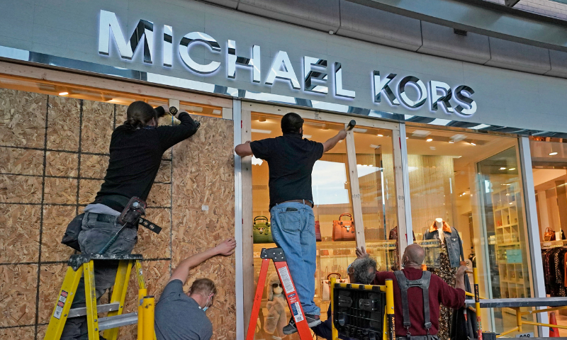 Workers board up the windows of Michael Kors in City Creek Center on Monday in Salt Lake City, US, ahead of Election Day. — AP