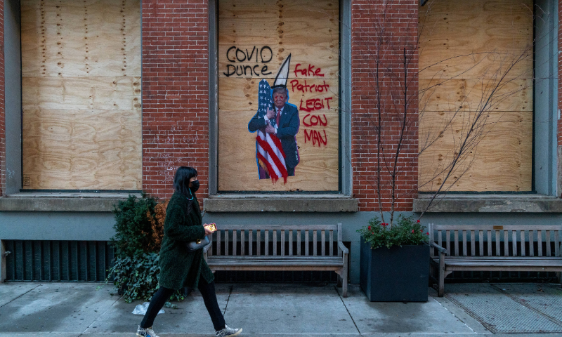 A person walks by boarded windows with a graffiti of President Donald Trump on Nov 2 in New York City. Property owners are preparing and boarding up store fronts as local and state officials warn of violence across the country on Election Day. — AFP