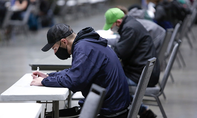 People fill out their ballots on Election Day at a voting centre for people that need to register or get other assistance in the vote-by-mail state in Seattle, Washington on November 3. — AFP