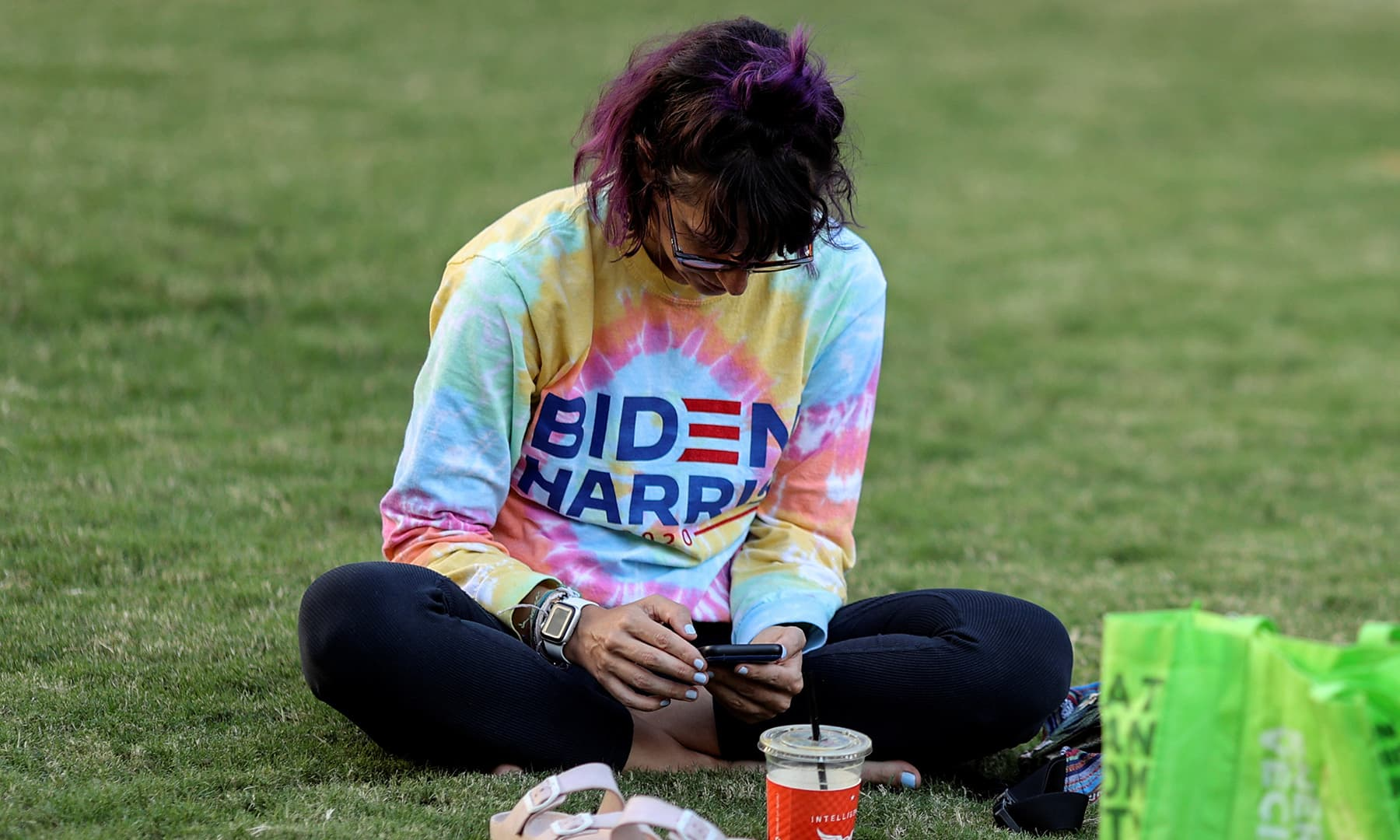 Biden supporter Jamie Sullivan, 36, checks her phone as she sits in a park in downtown Los Angeles on November 4. — Reuters