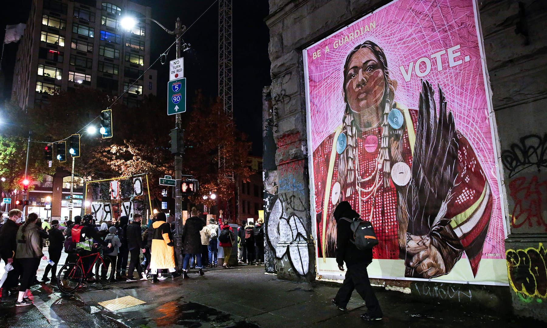 "Protestors walk past an image of a Native American woman during a march to ""Count Every Vote, Protect Every Person"" on the day after the US Presidential Election in Seattle on November 4. — AFP"