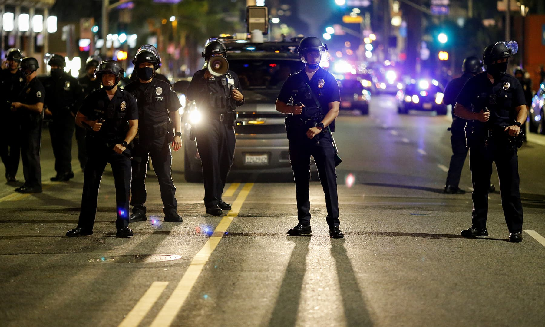 Police officers stand guard as they clear the streets during a protest in Los Angeles on November 4. — AP