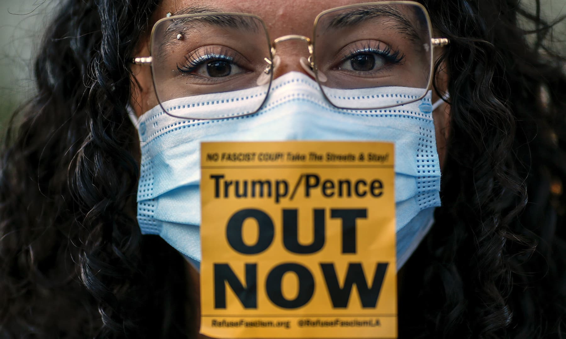 A woman wearing a face mask with a sticker takes part in a protest in Los Angeles on November 4. — AP