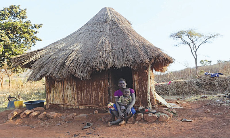 """A woman sits with her child outside her thatched hut on a farm in Zimbabwe. In a colossal betrayal of her family and home, Tambu creates a village safari to give European tourists an experience of the """"authentic"""" Africa 