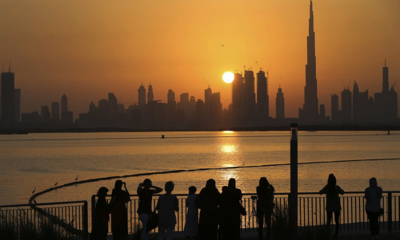 In this file photo, people watch the sunset over the skyline, with Burj Khalifa at right, in Dubai, United Arab Emirates. — AP