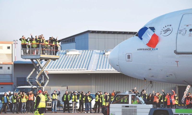 Airport personnel wave as an Air France flight prepares to take off from Berlin's Tegel Otto Lilienthal Airport on Sunday. It was the last plane to take off from the airport.—AFP