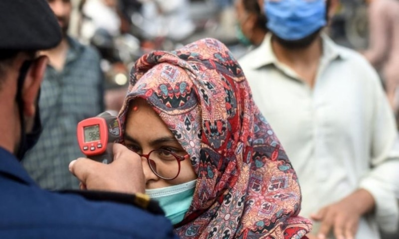 In this file photo, a shopping mall official checks the body temperature of a customer in Karachi. — AFP