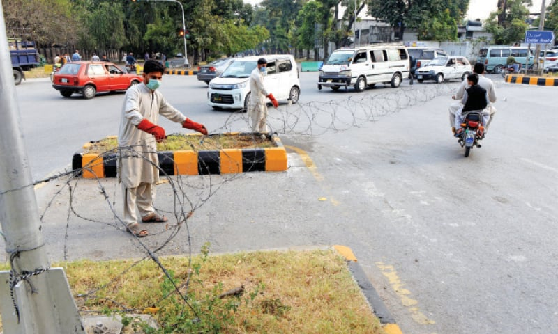 District administration officials place barbed wire on a road near Melody Chowk in G-6/2 following emergence of Covid-19 cases in the area. — Photo by Mohammad Asim