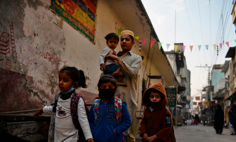 Children wearing facemask as a preventive measure against Covid-19 return from tuition in Rawalpindi on November 9. — AFP