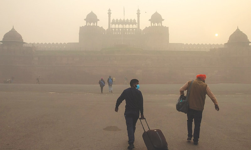 NEW DELHI: A few people pictured in front of the Red Fort on a smoggy morning. — Reuters