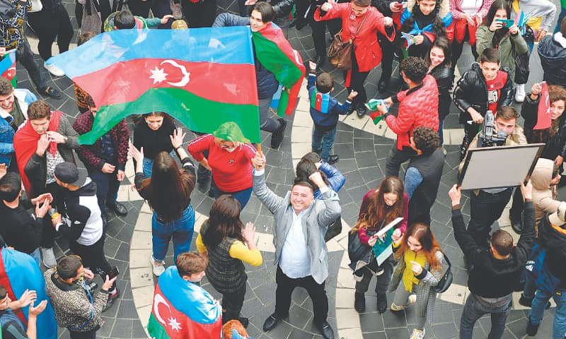 BAKU: Azerbaijanis wave the national flag as they celebrate on Tuesday after Armenia and Azerbaijan agreed to a ceasefire following a string of Azeri victories in fighting over the disputed Nagorno-Karabakh region.—AFP