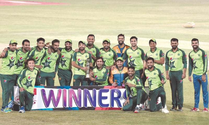 MEMBERS of Pakistan squad pose for a group photo with the series trophy after winning the third Twenty20 International against Zimbabwe at the Pindi Cricket Stadium on Tuesday. — Tanveer Shahzad/White star
