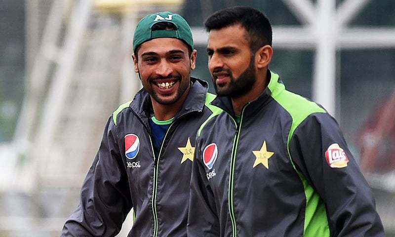 Mohammad Amir (L) shares a light moment with teammate Shoaib Malik during a team practice session in Lahore on January 6, 2016. — AFP/File