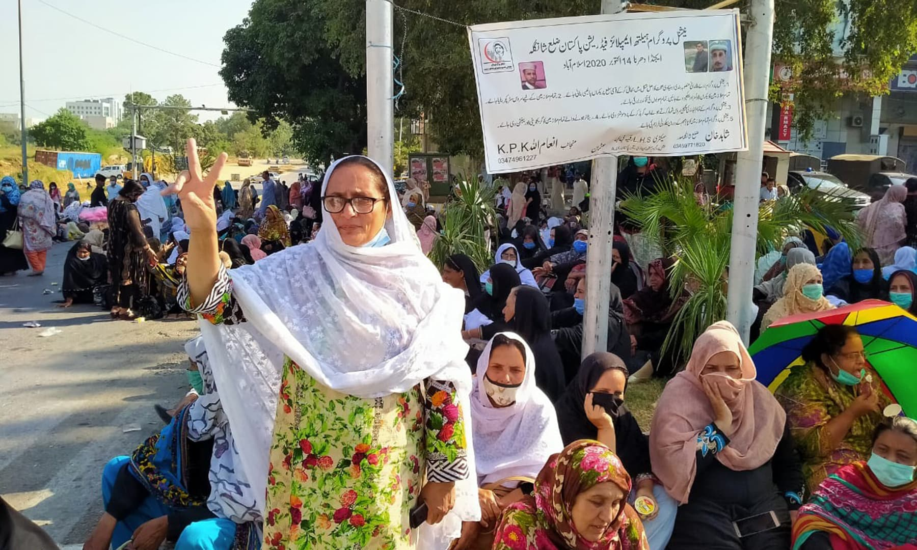 A Lady Health Worker flashes the victory sign during a protest in Islamabad. — Photo by author