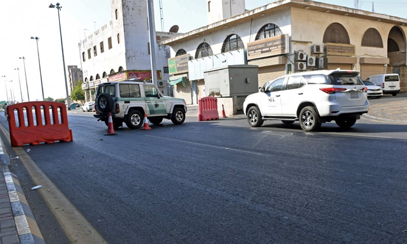 Police closing a street leading to the cemetery after the bomb blast.—AFP