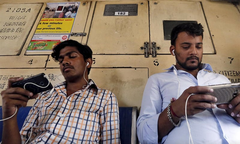 In this 2016 file photo, commuters watch videos on their mobile phones as they travel in a train in Mumbai. — Reuters