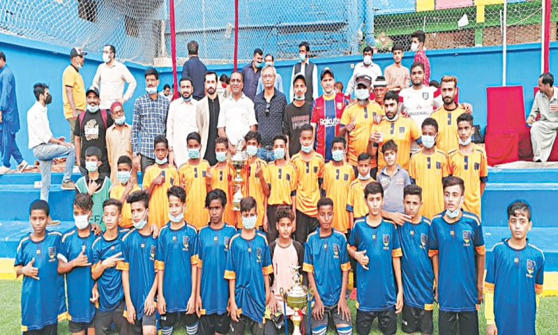 YOUNG footballers pose for a group photo with Irshad Ali Sodhar, Habib Hasan, Azfar Naqvi, Humayun Saghir and others at the inauguration of the refurbished Coach Emad Football Academy on Thursday.