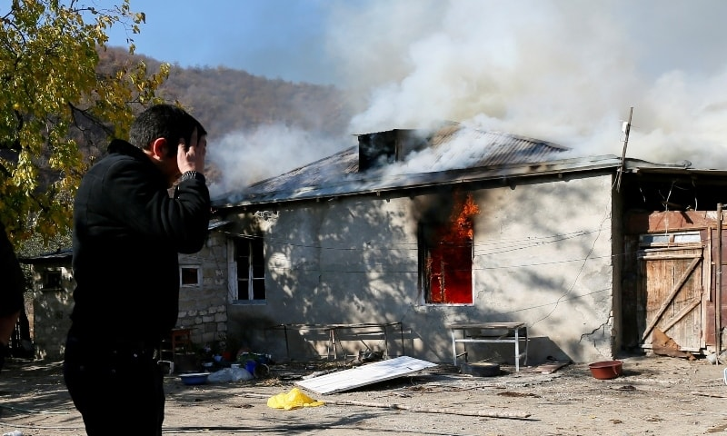 A man reacts as he stands near a house set on fire by departing ethnic Armenians, in an area which was held under their military control but is soon to be turned over to Azerbaijan, in the village of Cherektar in the region of Nagorno-Karabakh, November 14. — Reuters