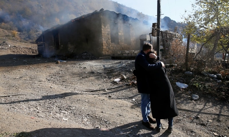 Residents hug as they stand near a house set on fire by departing ethnic Armenians in the village of Cherektar in the region of Nagorno-Karabakh, November 14. — Reuters