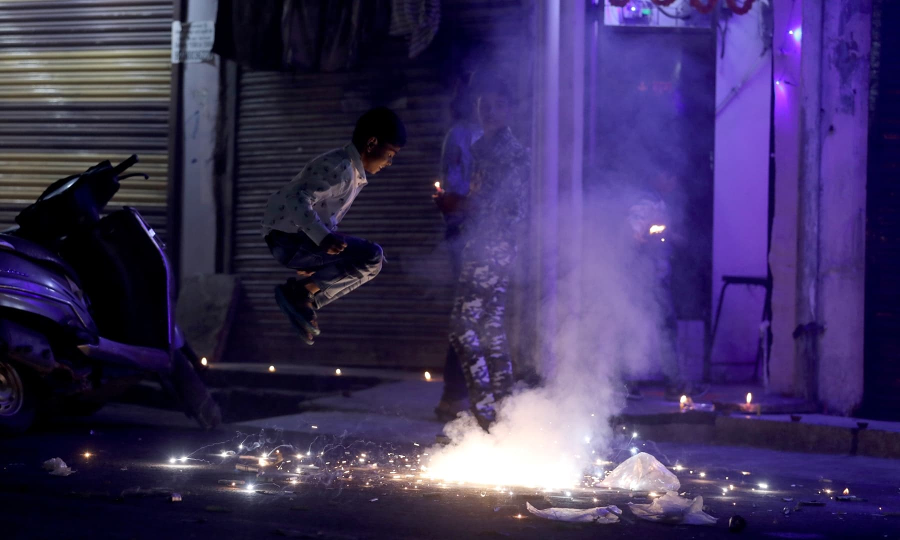 People watch as firecrackers burn during Diwali, the Hindu festival of lights, in New Delhi, India, November 14. — Reuters