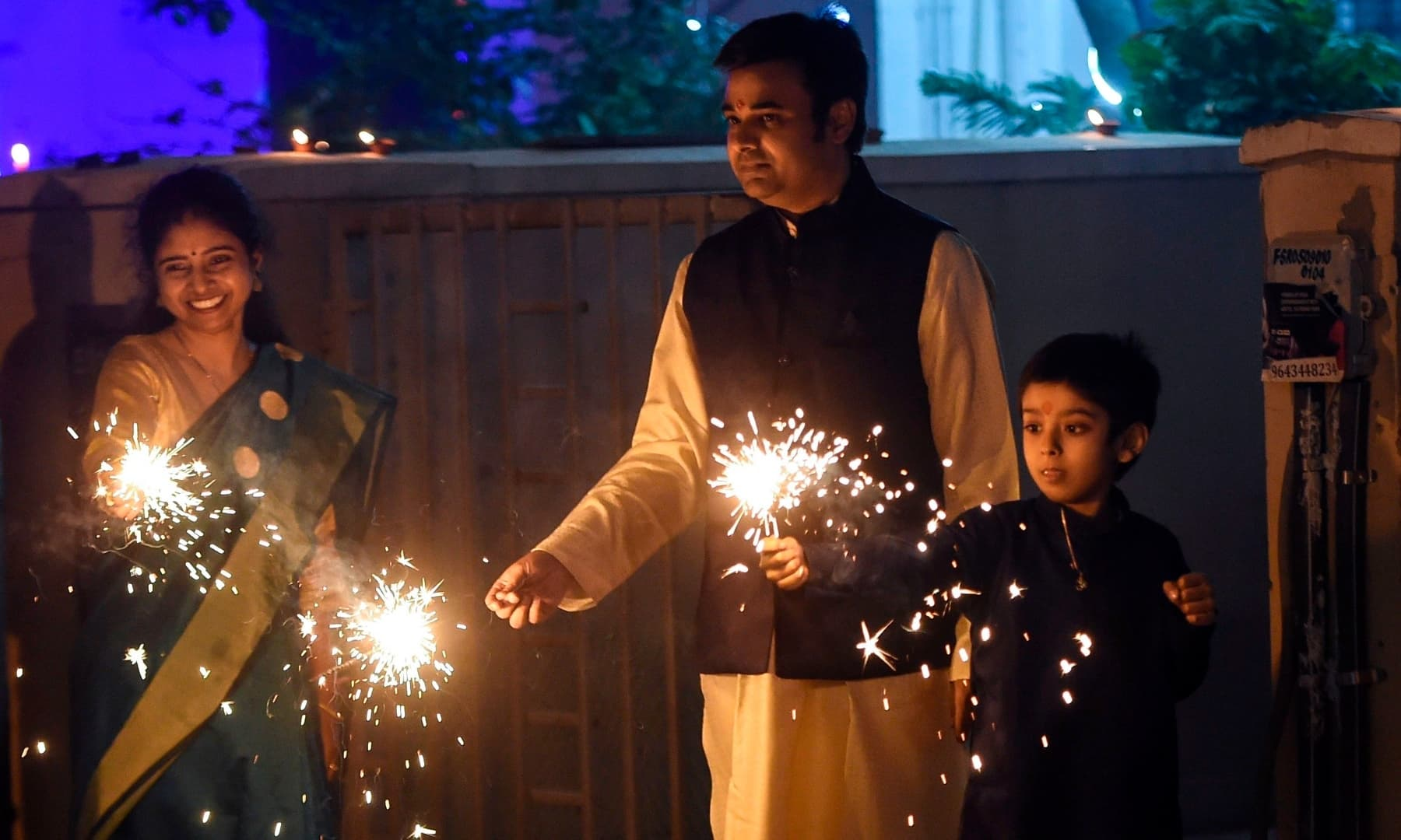 A family lights a sparkler during Diwali in Faridabad, India on Saturday. — AFP