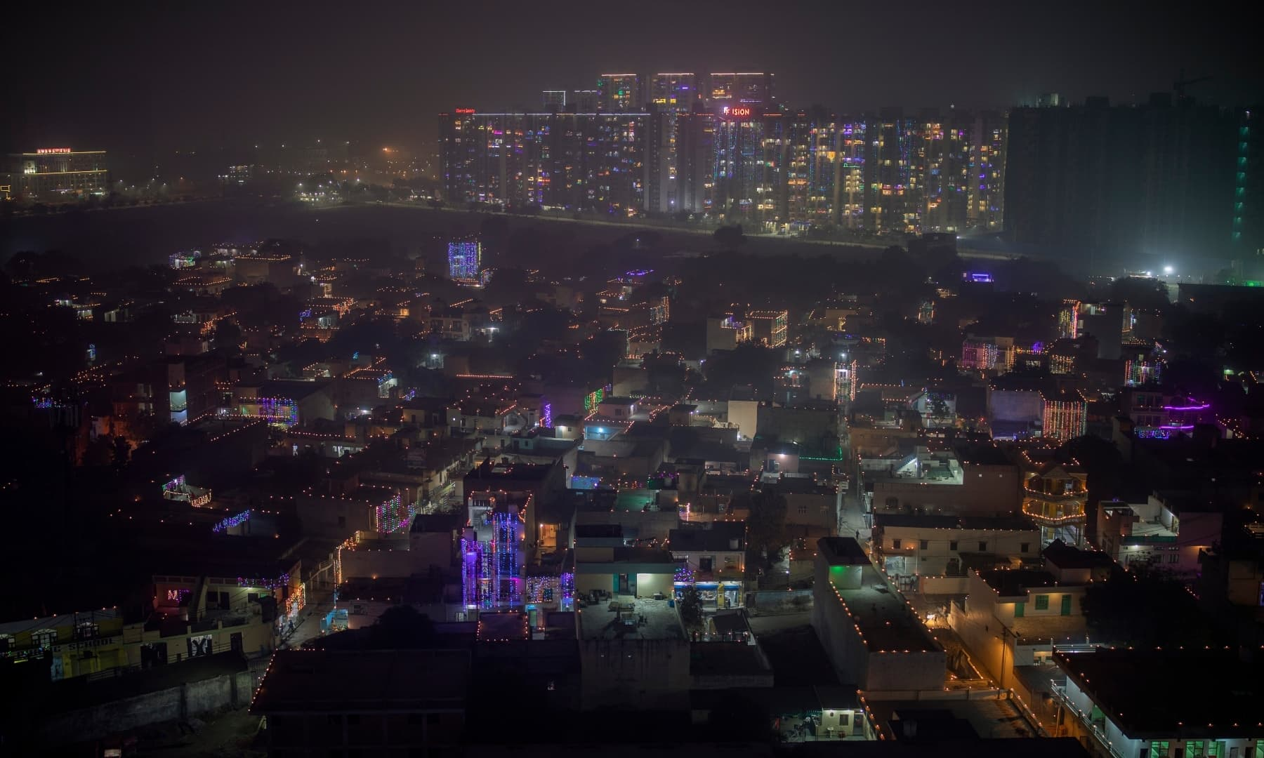 A layer of smog envelops the skyline as residential buildings are decorated with colourful lights during Diwali on the outskirts of New Delhi, India, Saturday. — AP
