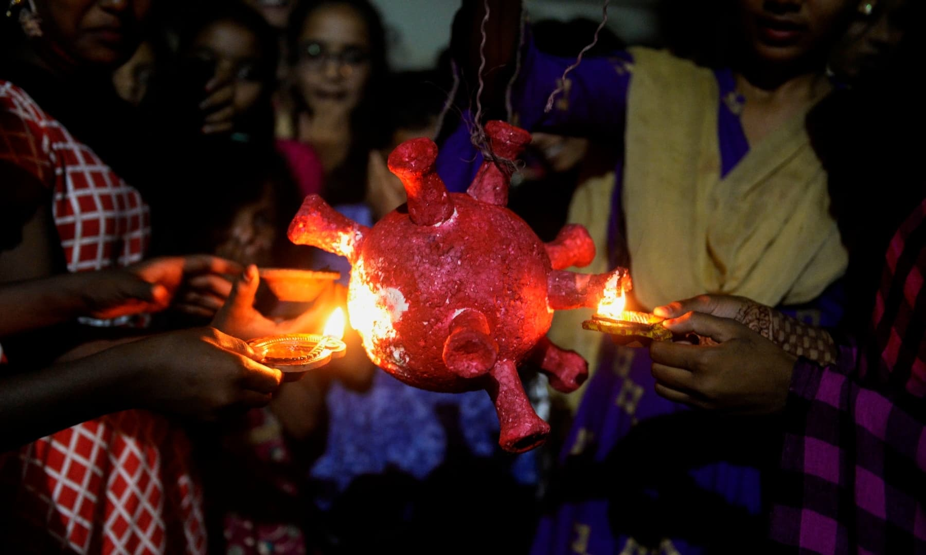 Students from the government girls hostel prepare to burn a Covid-19 coronavirus model during Diwali in Hyderabad, India. — AFP