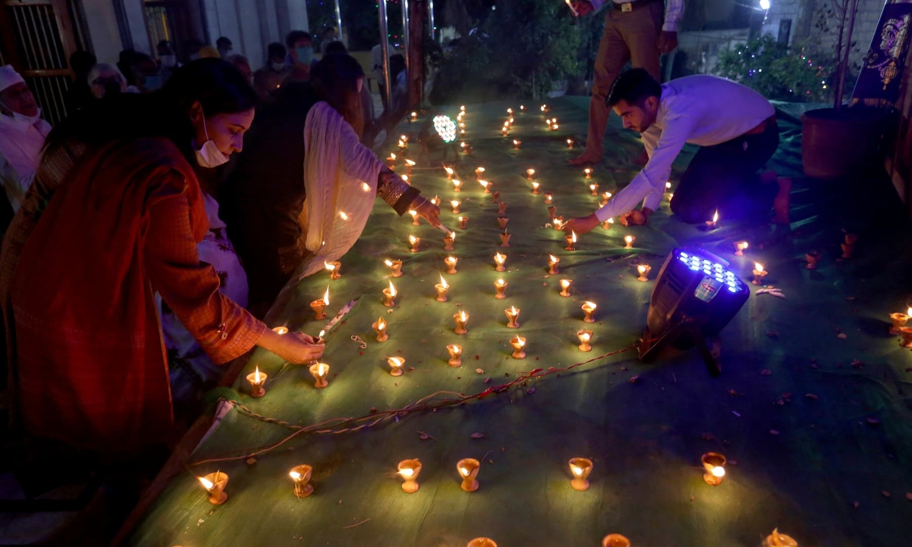 A Hindu family lights clay lamps during a ceremony to celebrate Diwali at Swami Narayan temple in Karachi, Saturday. — AP