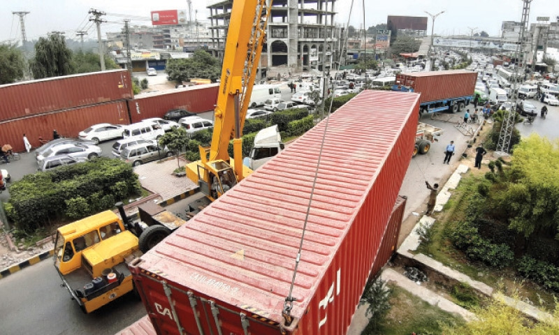 The district administration places containers at Faizabad on Saturday ahead of the TLP rally which will commence from Liaquat Bagh and end at Faizabad on Sunday. — Photo by Tanveer Shahzad