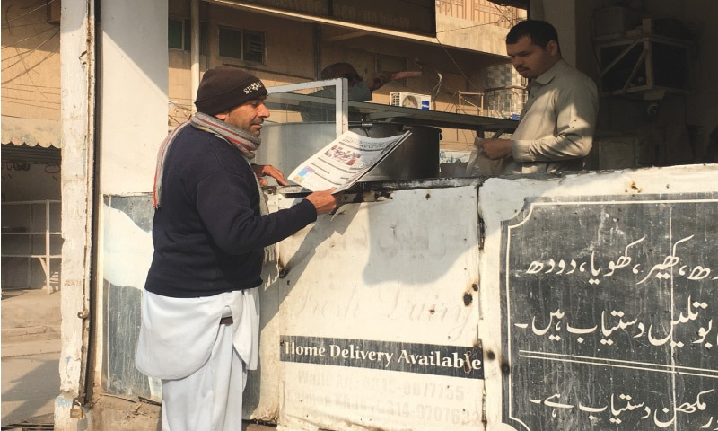 At the newspaper stall, Ijaz Ali collects the bundle of papers to deliver