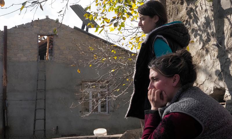Sirarpi Safaryan, foreground, sits near her house in Kalbajar before leaving the separatist region of Nagorno-Karabakh for Armenia. — Reuters
