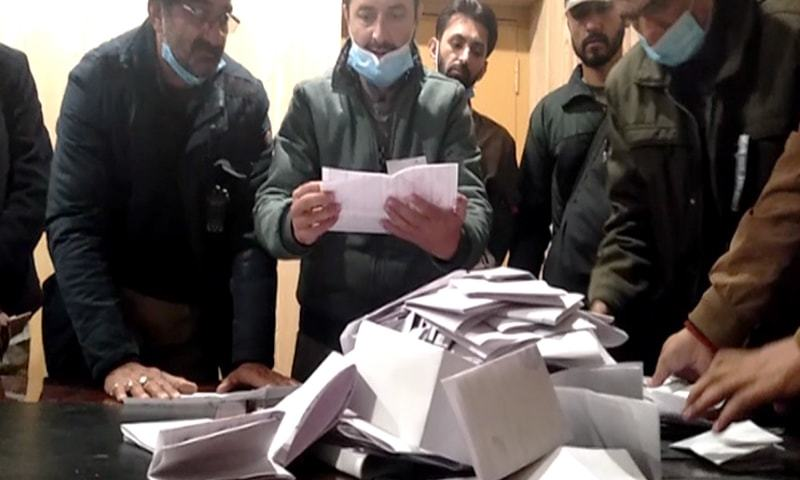 Staff at a polling station in GB count votes after polling comes to an end. — DawnNewsTV