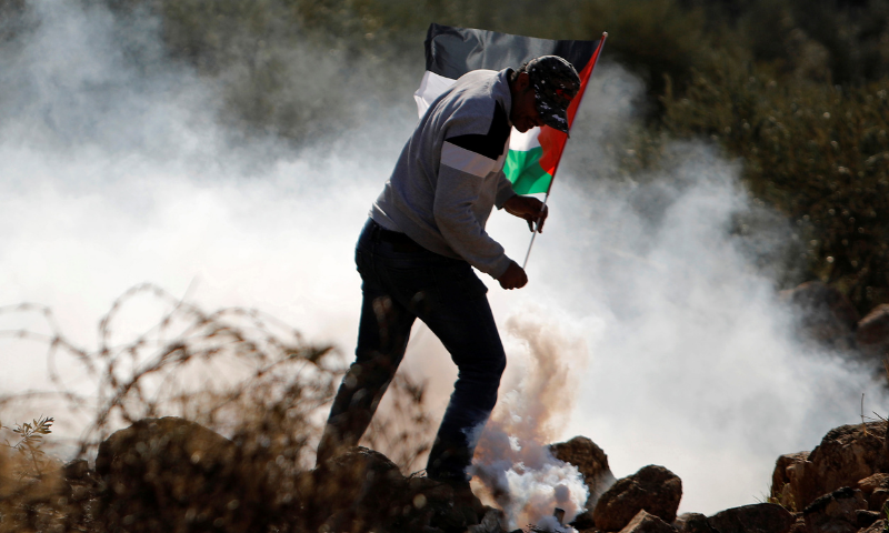 A Palestinian demonstrator runs a way from tear gas fired by Israeli forces during a protest against Jewish settlements, in Beit Dajan in the Israeli-occupied West Bank on Nov 13. — Reuters