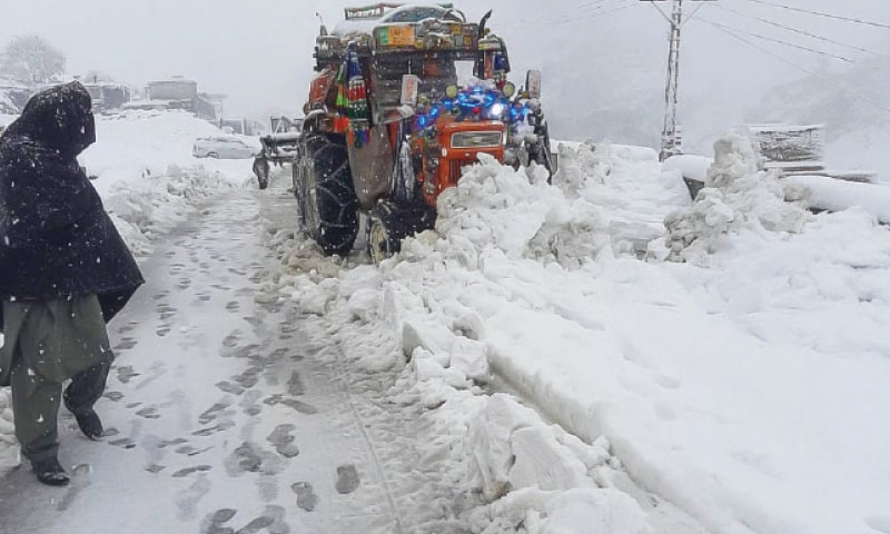 A tractor clears snow from Bahrain-Kalam Road in Swat on Sunday. — Dawn