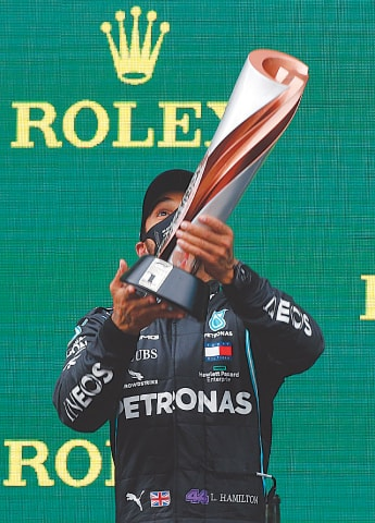 ISTANBUL: Mercedes driver Lewis Hamilton of Britain lifts his trophy as he lifcelebrates after winning the Turkish Formula One Grand Prix and the world championship here on Sunday.—AP