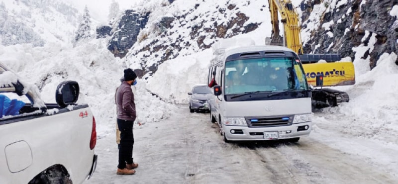 Vehicles pass through MNJ Road after being cleared in the Palandrian area near Kaghan on Monday. — Dawn
