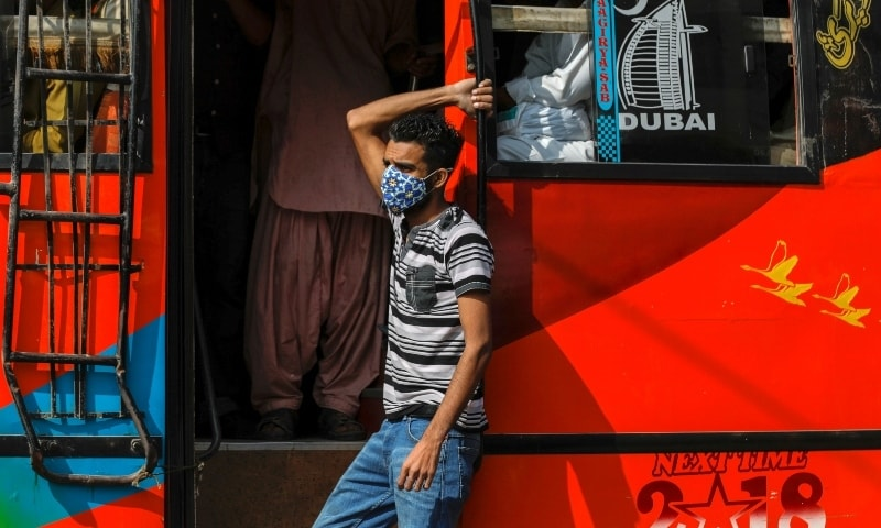 A man wears a protective mask as he rides on a bus in Karachi on Nov 16. — Reuters