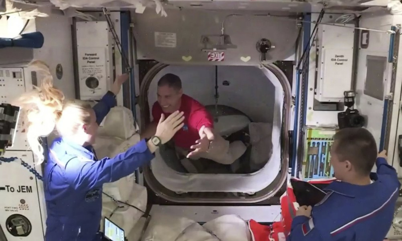 In this frame grab from NASA TV, astronaut Mike Hopkins, center, is greeted by astronaut Kate Rubins, left, as he enters the International Space Station from the vestibule between the SpaceX Dragon capsule and the ISS early on Tuesday. — AP