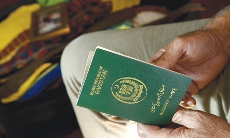 A Pakistani man checks his green passport. — APP/File